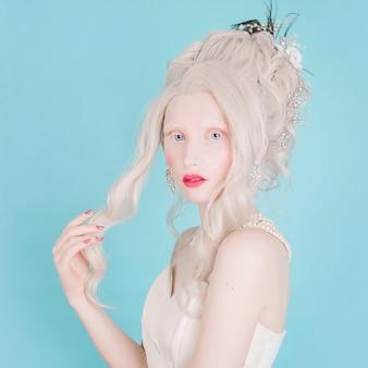 Mujer rubia con hermoso y lujoso peinado rococó en vestido blanco sobre un fondo azul.