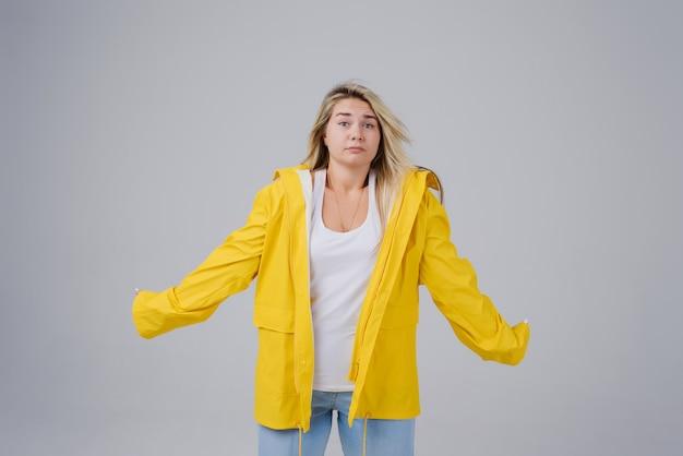 Mujer rubia con impermeable amarillo