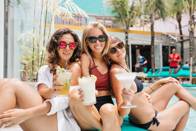 Mujer rubia inspirada en gafas negras divirtiéndose con hermanas durante el descanso de verano. tiro al aire libre de modelos femeninos caucásicos con vasos de cóctel relajante en fin de semana.