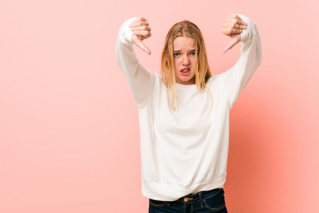 Mujer rubia joven del adolescente que muestra el pulgar hacia abajo y que expresa aversión.
