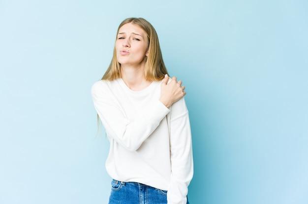 Mujer rubia joven aislada en la pared azul que tiene un dolor de hombro.