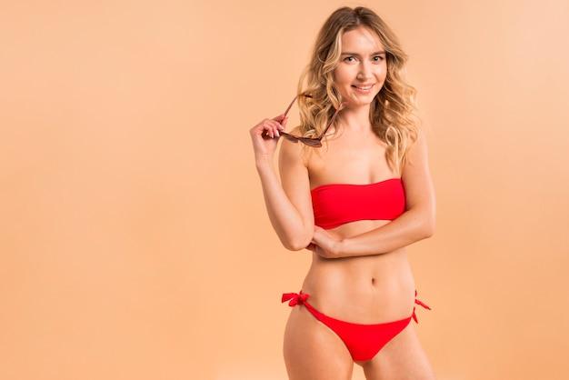 Mujer rubia joven en bikini rojo en fondo anaranjado