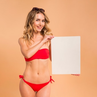 Mujer rubia joven en bikini rojo con papel en blanco