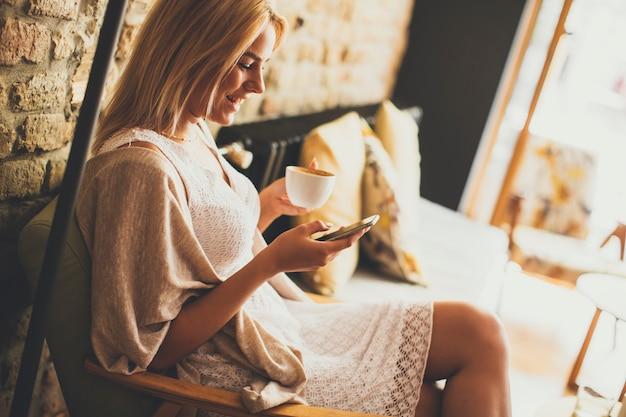 Mujer rubia joven en el café