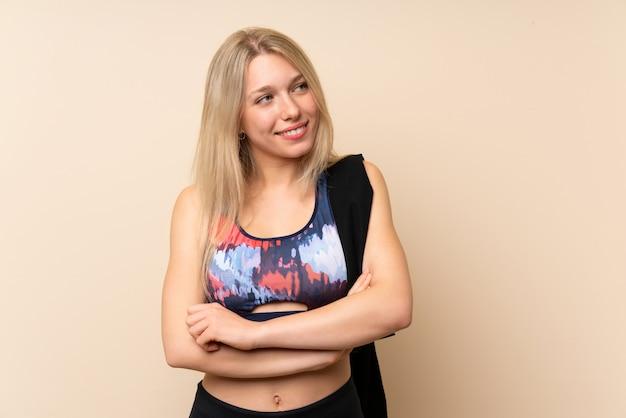 Mujer rubia joven del deporte sobre la pared aislada que mira al lado