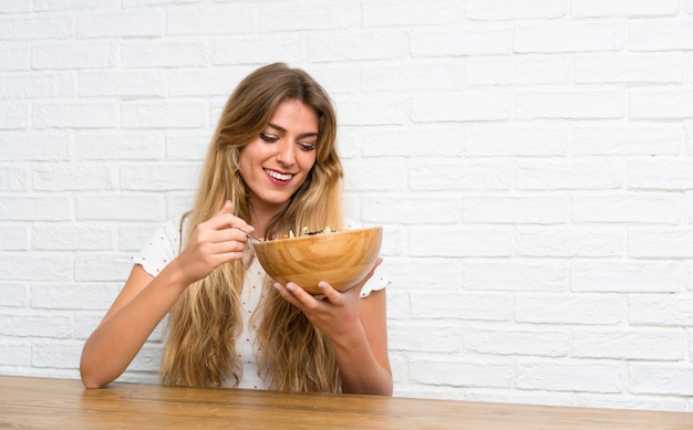 Mujer rubia joven feliz con la ensalada