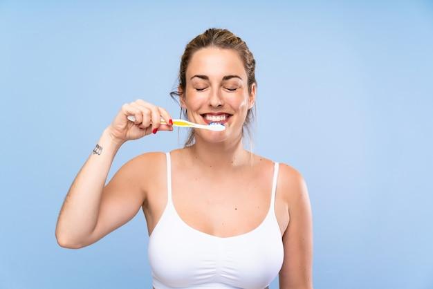 Mujer rubia joven feliz que cepilla sus teeths