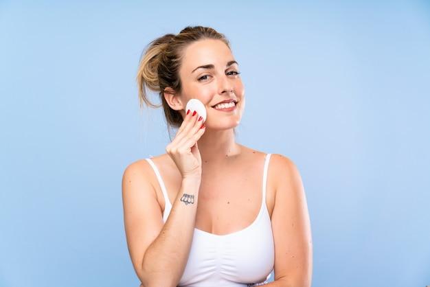 Mujer rubia joven feliz que quita maquillaje de su cara con algodón