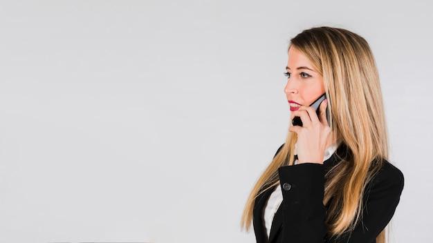 Mujer rubia joven hermosa que habla en el teléfono móvil contra fondo gris