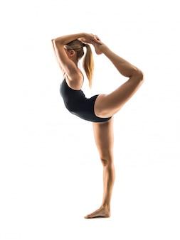 Mujer rubia joven en la lección practicante de la yoga del maillot