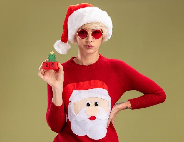 Mujer rubia joven molesta con sombrero de navidad y suéter de navidad de santa claus con gafas manteniendo la mano en la cintura sosteniendo el juguete del árbol de navidad con fecha mirando aislado en pared verde oliva