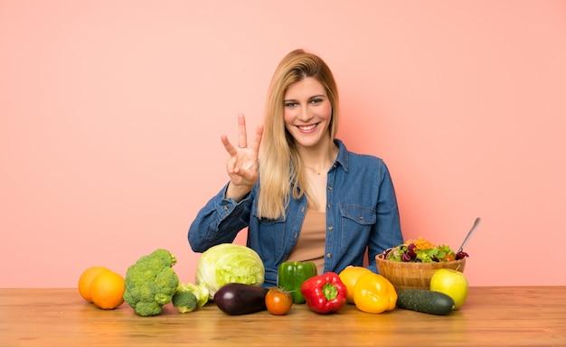 Mujer rubia joven con muchas verduras felices y contando tres con los dedos