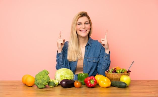 Mujer rubia joven con muchas verduras que señala una gran idea