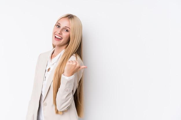 La mujer rubia joven del negocio en la pared blanca señala con el dedo del pulgar lejos, riendo y despreocupado.