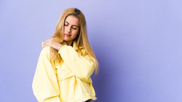 Mujer rubia joven en la pared púrpura que tiene un dolor de hombro.