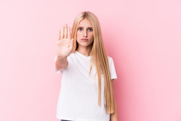 Mujer rubia joven en la pared rosada que se coloca con la mano extendida que muestra la señal de stop, previniéndole.