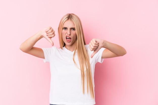 Mujer rubia joven en la pared rosada que muestra el pulgar hacia abajo y que expresa aversión.