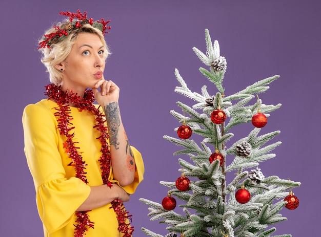 Mujer rubia joven pensativa con corona de navidad y guirnalda de oropel alrededor del cuello de pie cerca del árbol de navidad decorado manteniendo la mano en la barbilla mirando hacia arriba aislado sobre fondo púrpura
