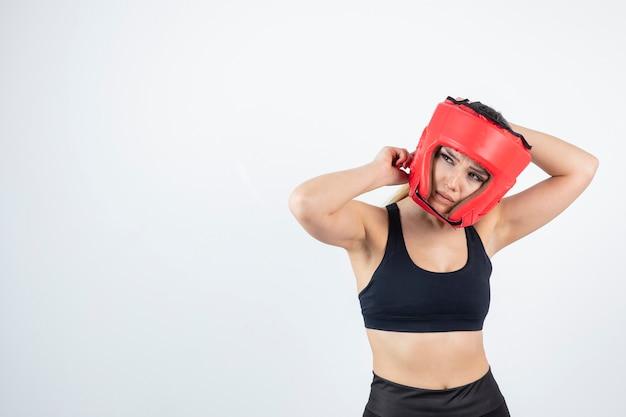Mujer rubia joven en la presentación del casco de boxeo rojo.