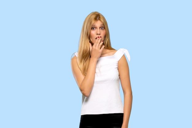 Mujer rubia joven que cubre la boca con las manos por decir algo inapropiado