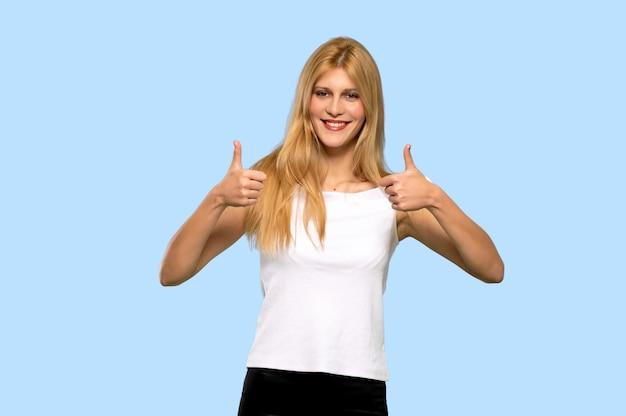 Mujer rubia joven que da un pulgar hacia arriba gesto porque algo bueno ha sucedido en el fondo azul aislado