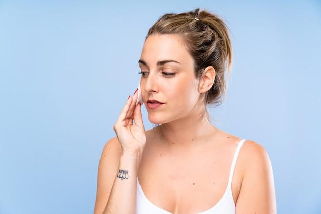 Mujer rubia joven que quita maquillaje de su cara con el cojín de algodón