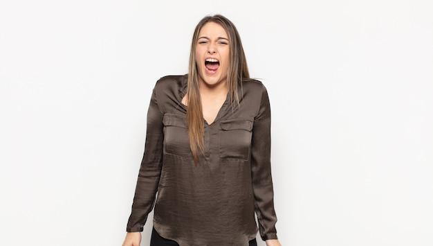 Mujer rubia joven que se siente aterrorizada y conmocionada, con la boca abierta por la sorpresa