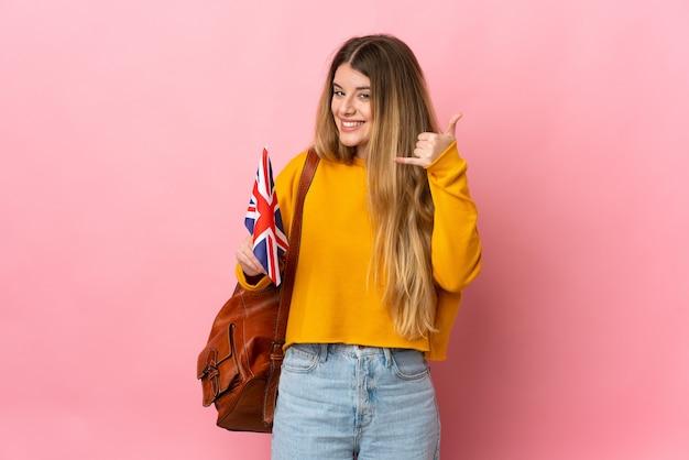 Mujer rubia joven que sostiene una bandera del reino unido aislada en la pared blanca que hace el gesto del teléfono. llámame señal