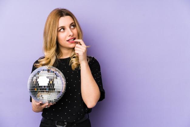 Mujer rubia joven que sostiene una bola del partido de la noche aislada relajada pensando en algo mirando un espacio de la copia.