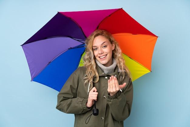 Mujer rubia joven que sostiene un paraguas aislado en la pared azul que invita a venir con la mano. feliz de que hayas venido