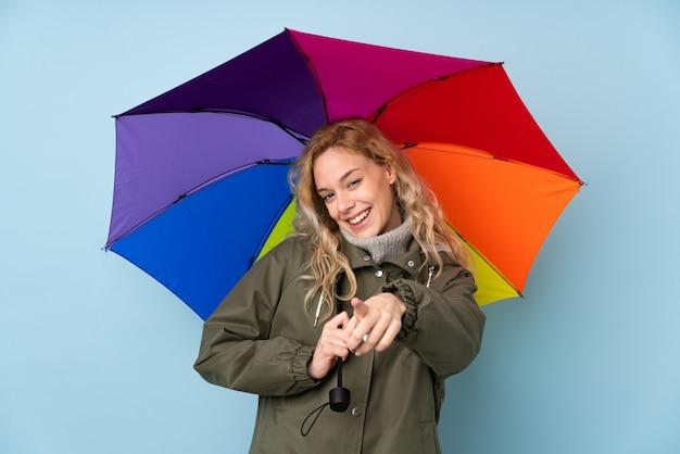 La mujer rubia joven que sostiene un paraguas aislado en la pared azul le señala con el dedo con una expresión confiada
