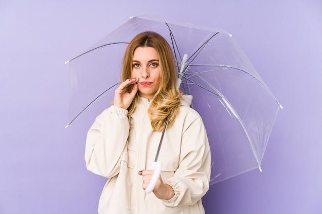 Mujer rubia joven que sostiene un paraguas con los dedos en los labios que guardan un secreto.