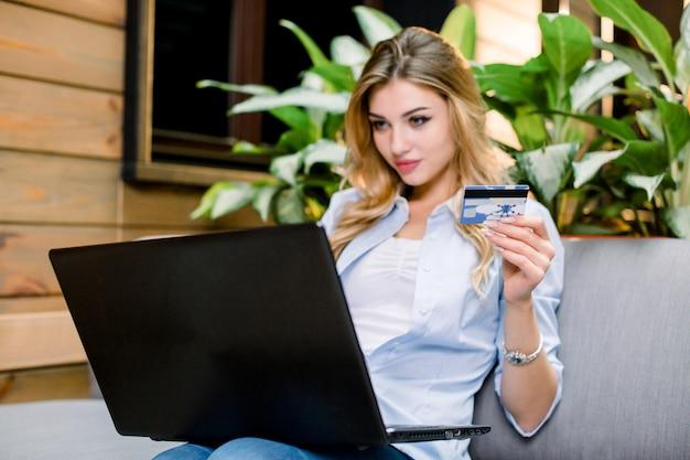 Mujer rubia joven que sostiene la tarjeta de crédito y que usa la computadora portátil.
