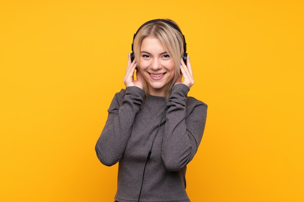 Mujer rubia joven sobre música que escucha aislada de la pared amarilla