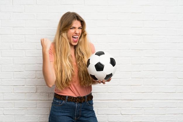 Mujer rubia joven sobre la pared de ladrillo blanca que sostiene un balón de fútbol