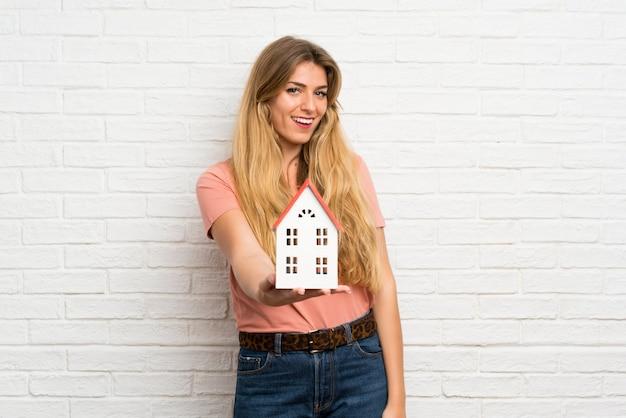 Mujer rubia joven sobre la pared de ladrillo blanca que sostiene una pequeña casa