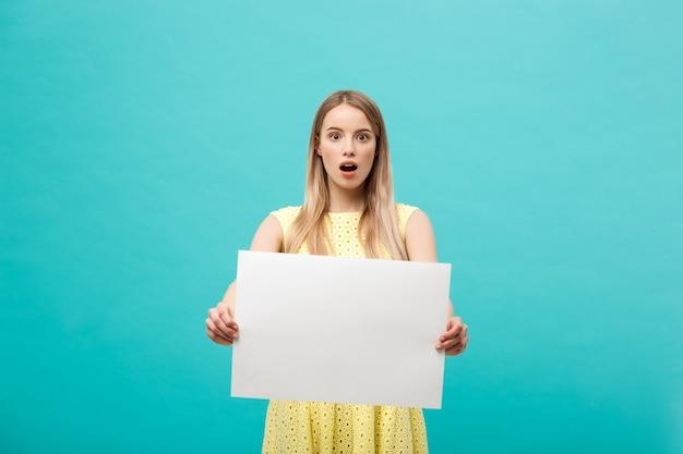 Mujer rubia joven sorprendida que lleva a cabo la muestra en blanco con el espacio de la copia en fondo azul del estudio.