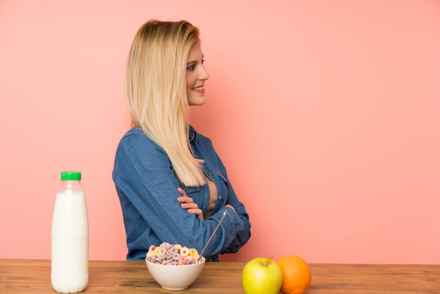 Mujer rubia joven con tazón de cereales de pie y mirando hacia el lado