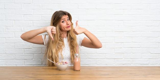 Mujer rubia joven con un tazón de cereales que hace buena y mala señal