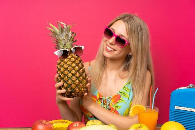 Mujer rubia joven en el traje de baño que sostiene una piña con las gafas de sol