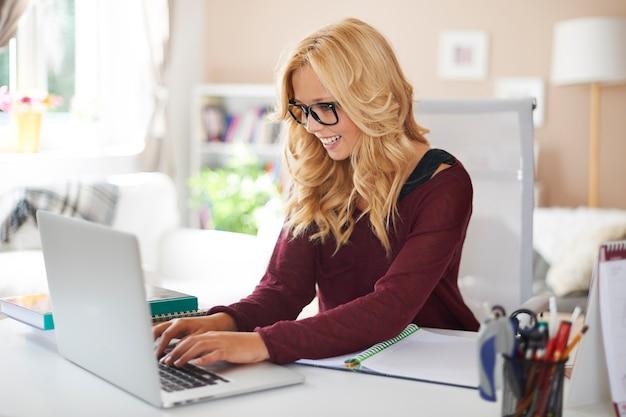 Mujer rubia con laptop en casa