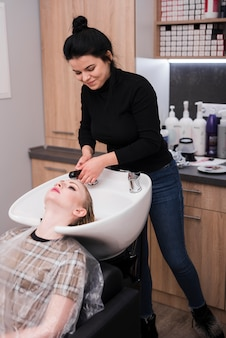 Mujer rubia lavándose el pelo
