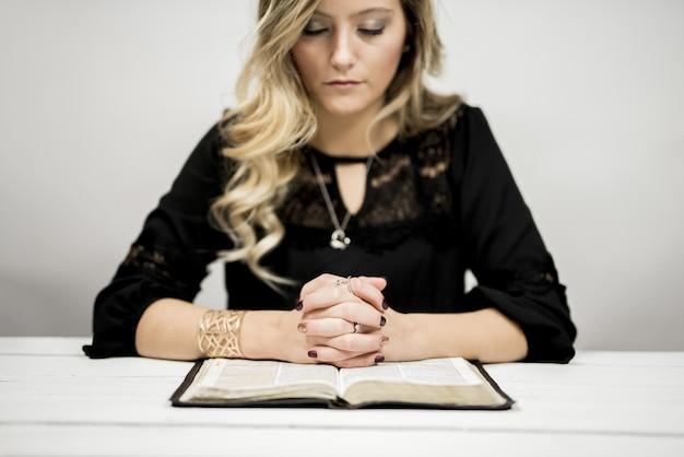 Mujer rubia leyendo la biblia y rezando