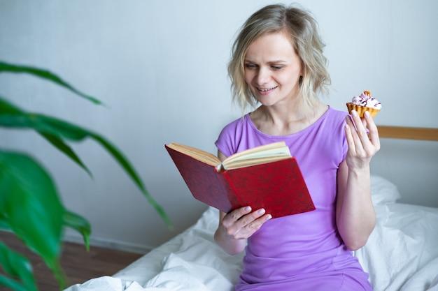 Mujer rubia con libro abierto y leyendo acostado en la cama con pastel en la mano. ocio, quedarse en casa y cuarentena. tiempo para ti