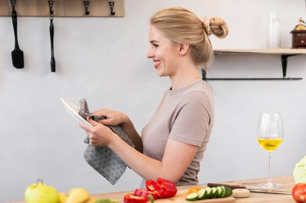 Mujer rubia limpiando el plato