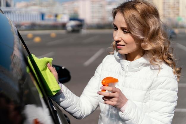 Mujer rubia limpiando su coche