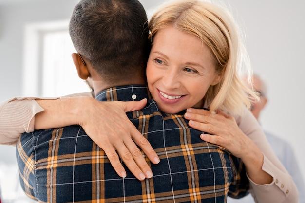 Mujer rubia madura abrazando a uno de los compañeros de sesión de psicoterapia mientras expresa su atención y apoyo