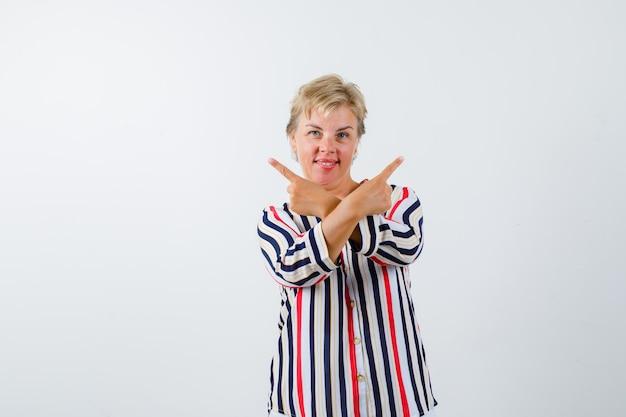 Mujer rubia madura en una camisa de rayas verticales
