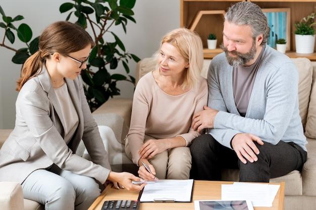 Mujer rubia madura escuchando al joven agente inmobiliario confiado mientras va a firmar el contrato en la oficina