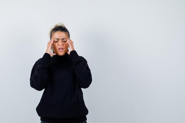 Mujer rubia con las manos en la cara en suéter negro y mirando disgustado, vista frontal.
